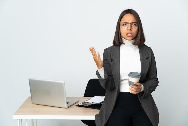 Молодая латинская деловая женщина, работающая в офисе, изолированном на белом фоне, делает жест сомнения