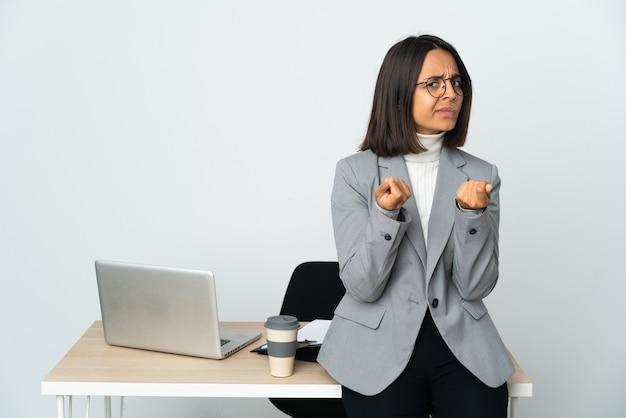 Молодая латинская деловая женщина, работающая в офисе, изолированном на белом фоне, делает денежный жест, но разрушена