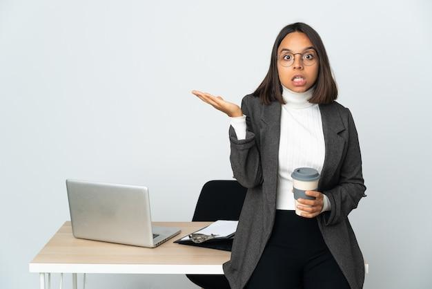 Молодая латинская деловая женщина, работающая в офисе, изолированном на белом фоне, делая телефонный жест и сомневаясь