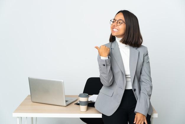 제품을 제시하는 측면을 가리키는 흰색 배경에 고립 된 사무실에서 일하는 젊은 라틴 비즈니스 여자