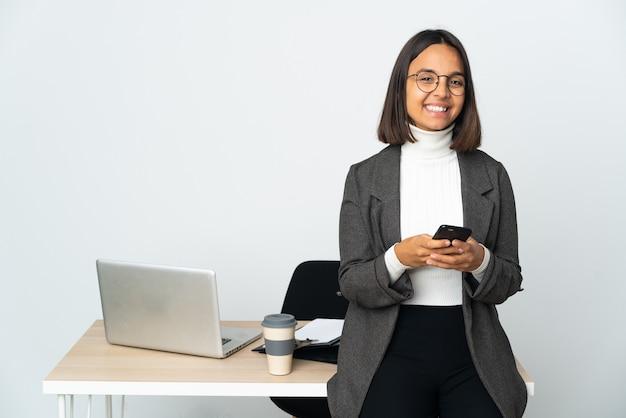 Молодая латинская деловая женщина, работающая в офисе, изолированном на белом фоне, отправляет сообщение с мобильного телефона
