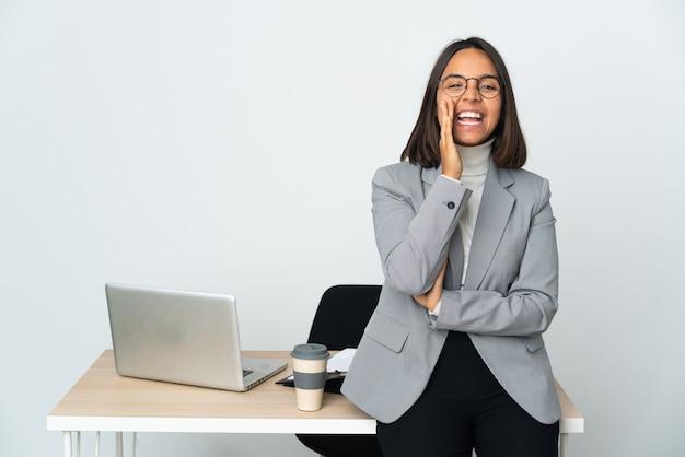 Молодая латинская деловая женщина, работающая в офисе, изолированном на белом фоне, кричит с широко открытым ртом