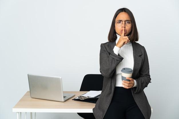 口に指を入れて沈黙ジェスチャーの兆候を示す白い背景で隔離のオフィスで働く若いラテンビジネス女性