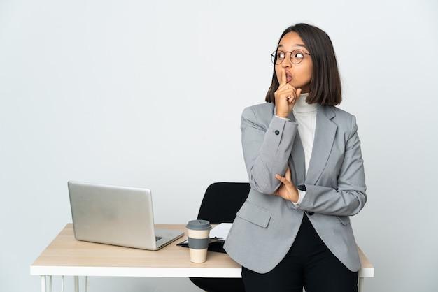 입에 손가락을 넣어 침묵 제스처의 기호를 보여주는 흰색 배경에 고립 된 사무실에서 일하는 젊은 라틴 비즈니스 여자