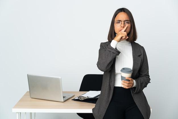 Молодая латинская деловая женщина, работающая в офисе, изолированном на белом фоне, показывает знак жеста молчания