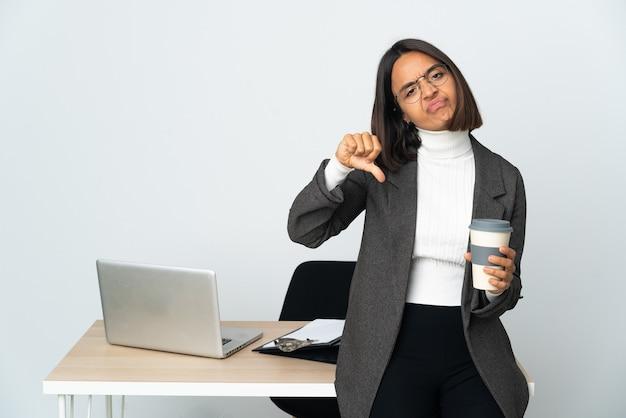 두 손으로 아래로 엄지손가락을 보여주는 흰색 배경에 고립 된 사무실에서 일하는 젊은 라틴 비즈니스 여자