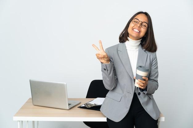 웃 고 승리 기호를 보여주는 흰색 배경에 고립 된 사무실에서 일하는 젊은 라틴 비즈니스 여자