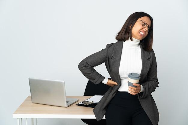 Молодая латинская деловая женщина, работающая в офисе, изолированном на белом фоне, страдает от боли в спине за то, что приложила усилия