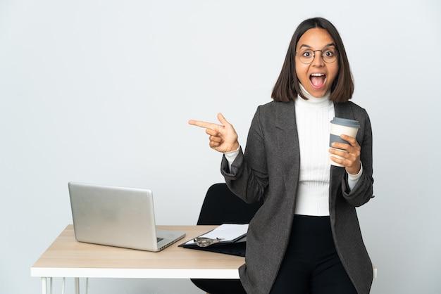 Молодая латинская деловая женщина, работающая в офисе, изолированном на белом фоне, удивлена и указывает сторону