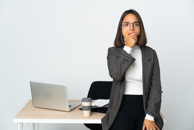 Молодая латинская деловая женщина, работающая в офисе, изолированном на белом фоне, удивлена и шокирована, глядя вправо