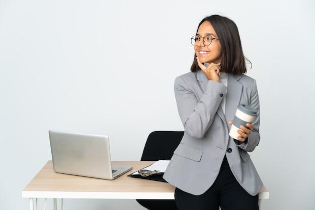 찾는 동안 아이디어를 생각하는 흰색 배경에 고립 된 사무실에서 일하는 젊은 라틴 비즈니스 여자