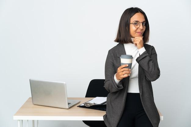 흰색 배경 생각에 고립 된 사무실에서 일하는 젊은 라틴 비즈니스 우먼