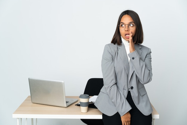 Молодая латинская деловая женщина, работающая в офисе, изолированном на белом фоне, шепчет что-то с удивленным жестом, глядя в сторону