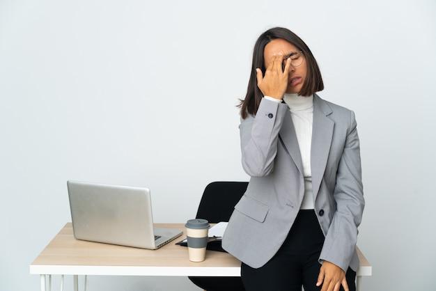 Молодая латинская деловая женщина, работающая в офисе, изолированном на белом фоне с головной болью