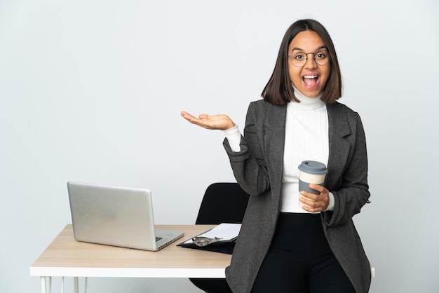 Молодая латинская деловая женщина, работающая в офисе на белом фоне с шокированным выражением лица