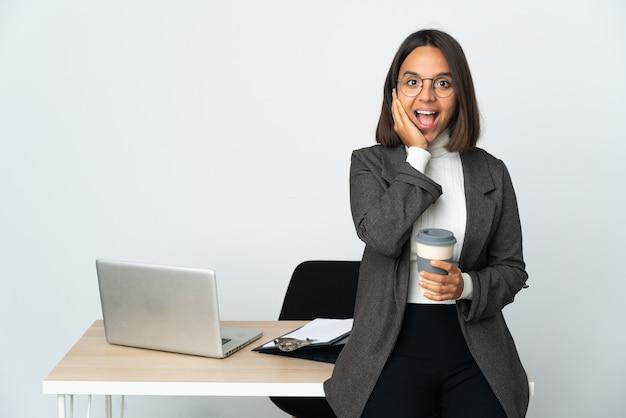 Молодая латинская деловая женщина, работающая в офисе, изолирована на белом фоне с удивленным и шокированным выражением лица