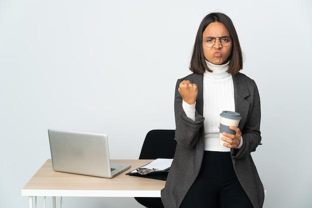 Молодая латинская деловая женщина, работающая в офисе, изолированном на белом фоне с несчастным выражением лица