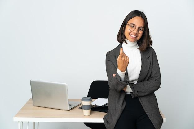 오는 제스처를 하 고 흰색에 고립 된 사무실에서 일하는 젊은 라틴 비즈니스 여자