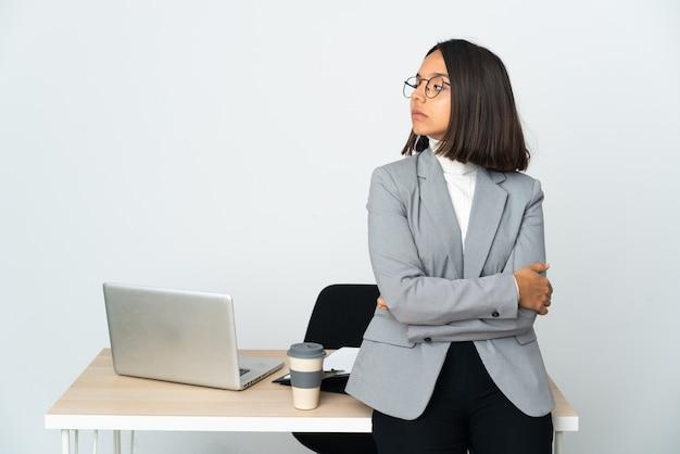 腕を組んで白で隔離のオフィスで働く若いラテンビジネス女性