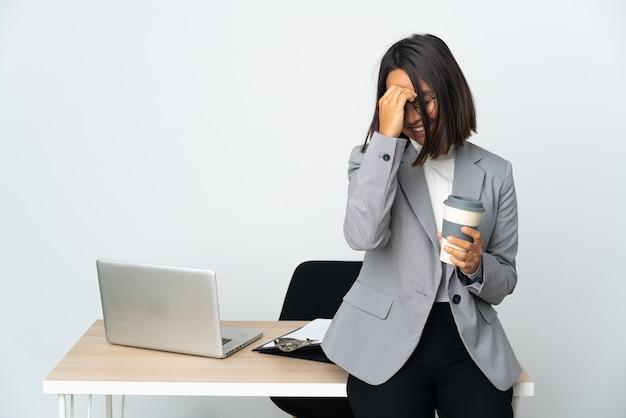흰색 웃음에 고립 된 사무실에서 일하는 젊은 라틴 비즈니스 여자