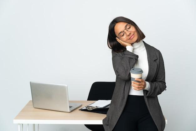 Dorable 식에서 수면 제스처를 만드는 흰색에 고립 된 사무실에서 일하는 젊은 라틴 비즈니스 여자
