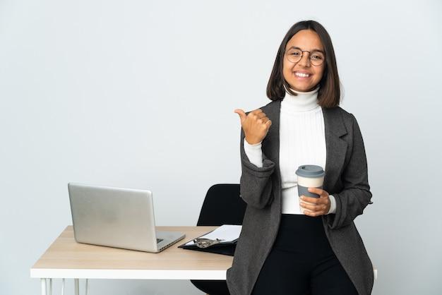 제품을 제시하는 측면을 가리키는 흰색에 고립 된 사무실에서 일하는 젊은 라틴 비즈니스 여자