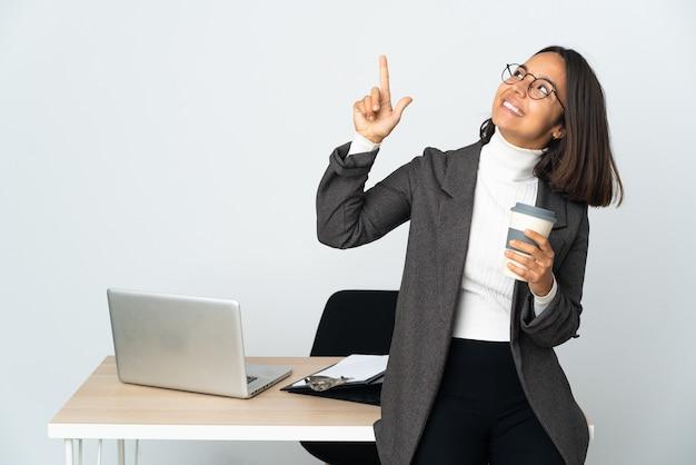 검지 손가락으로 좋은 아이디어를 가리키는 흰색에 고립 된 사무실에서 일하는 젊은 라틴 비즈니스 여자