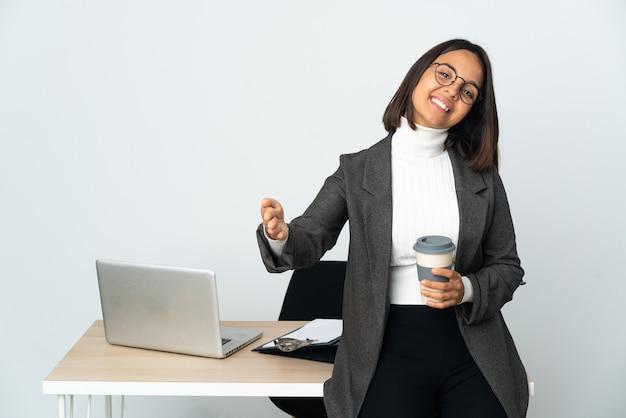 사무실에서 일하는 젊은 라틴 비즈니스 여자는 흰색 제시와 손으로 초대에 고립
