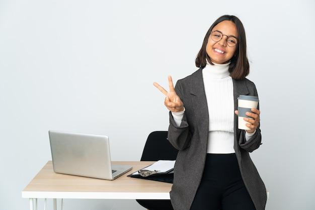 웃 고 승리 기호를 보여주는 흰색에 고립 된 사무실에서 일하는 젊은 라틴 비즈니스 여자