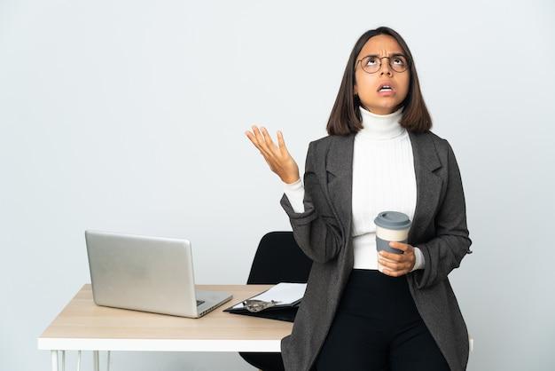 흰색에 고립 된 사무실에서 일하는 젊은 라틴 비즈니스 여자는 압도 스트레스