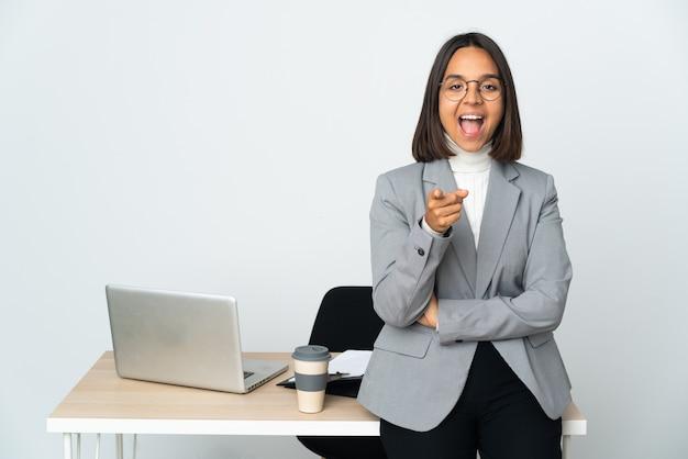 흰색 놀라게 하 고 앞을 가리키는에 고립 된 사무실에서 일하는 젊은 라틴 비즈니스 여자