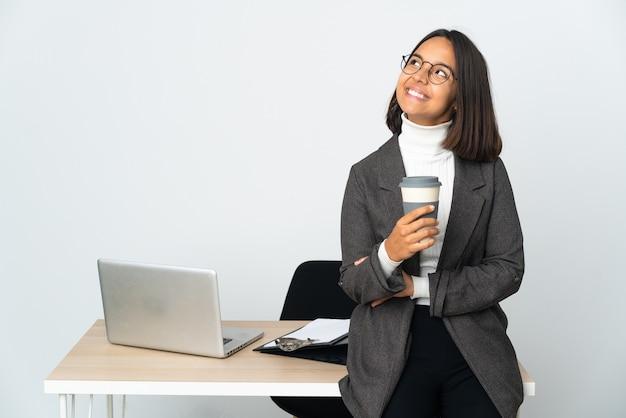 찾는 동안 아이디어를 생각하는 흰색에 고립 된 사무실에서 일하는 젊은 라틴 비즈니스 여자