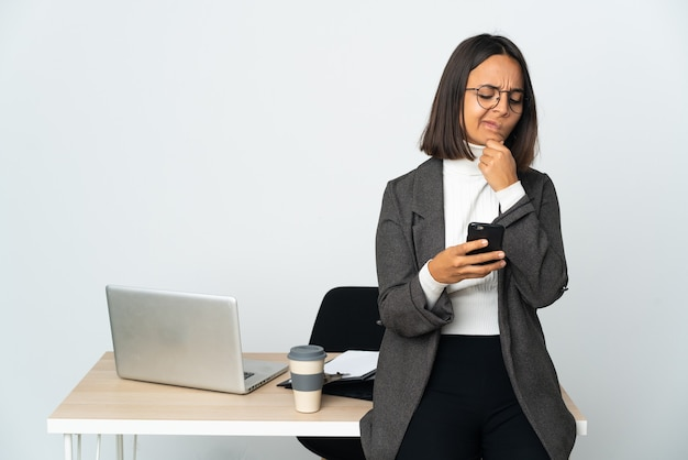 생각하고 메시지를 보내는 흰색에 고립 된 사무실에서 일하는 젊은 라틴 비즈니스 여자