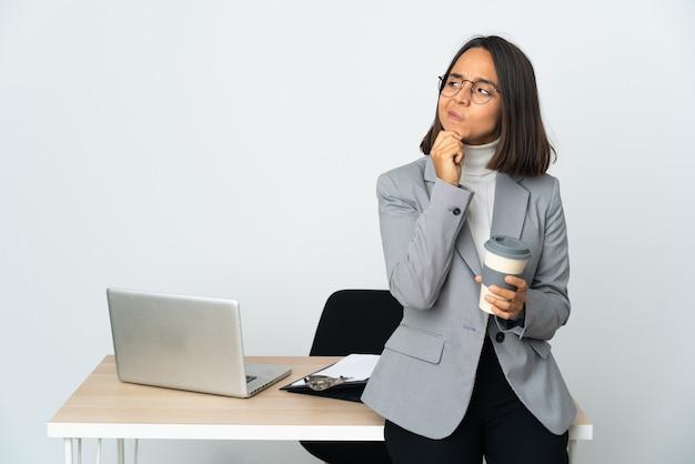 흰 벽에 고립 된 사무실에서 일하고 찾는 젊은 라틴 비즈니스 여자