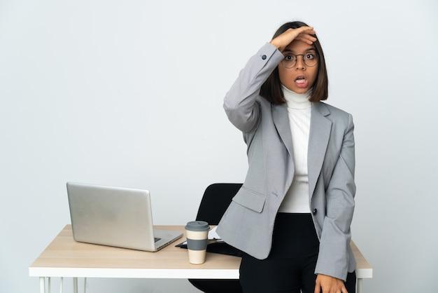 측면을 보면서 깜짝 제스처를 하 고 흰 벽에 고립 된 사무실에서 일하는 젊은 라틴 비즈니스 여자