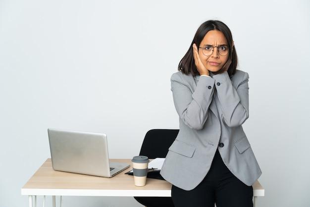 좌절과 귀를 덮고 흰 벽에 고립 된 사무실에서 일하는 젊은 라틴 비즈니스 여자
