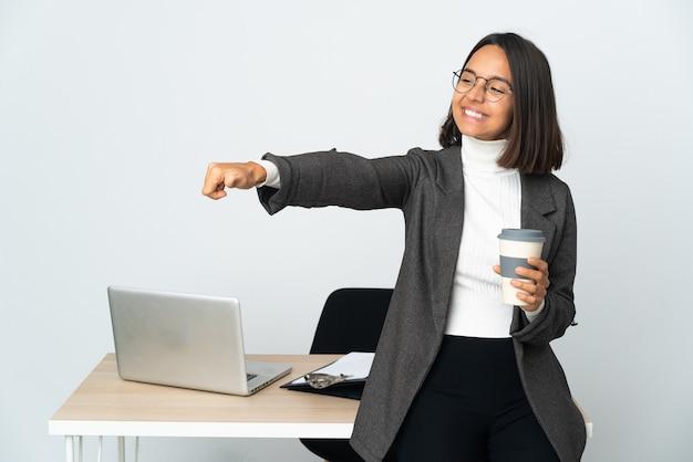제스처를 엄지 손가락을주는 흰 벽에 고립 된 사무실에서 일하는 젊은 라틴 비즈니스 여자