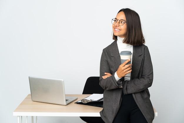 행복하고 웃는 흰 벽에 고립 된 사무실에서 일하는 젊은 라틴 비즈니스 여자