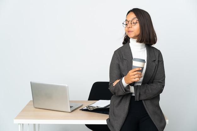 측면을 보면서 의심을 갖는 흰 벽에 고립 된 사무실에서 일하는 젊은 라틴 비즈니스 여자