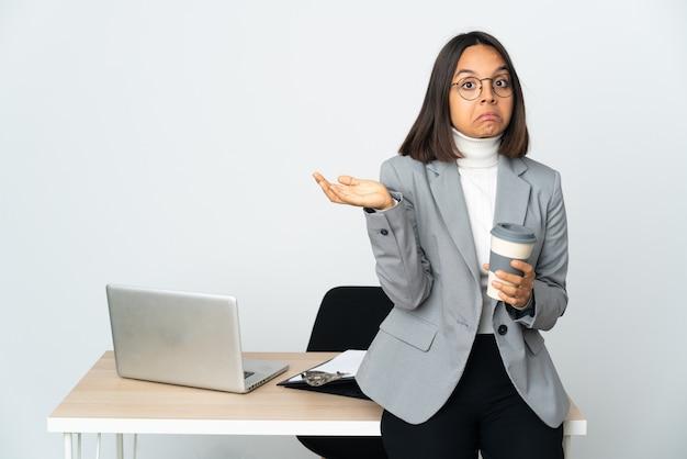 손을 올리는 동안 의심을 갖는 흰 벽에 고립 된 사무실에서 일하는 젊은 라틴 비즈니스 여자