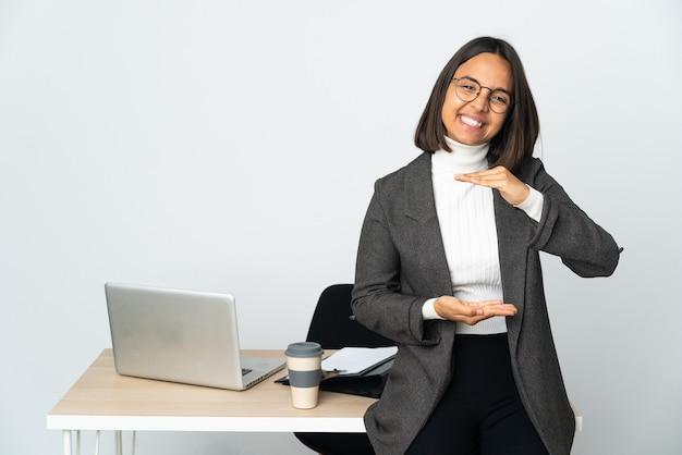 광고를 삽입하는 손바닥에 상상 copyspace 들고 흰 벽에 고립 된 사무실에서 일하는 젊은 라틴 비즈니스 여자