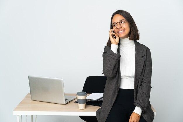 휴대 전화로 대화를 유지하는 흰 벽에 고립 된 사무실에서 일하는 젊은 라틴 비즈니스 여자