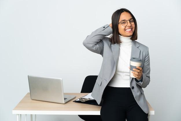 사무실에서 일하는 젊은 라틴 비즈니스 여자는 웃고 흰 벽에 고립