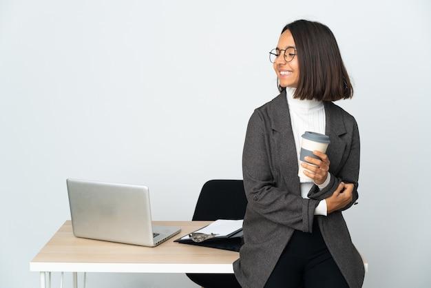 Молодая латинская деловая женщина, работающая в офисе, изолированном на белой стене, смотрит в сторону и улыбается