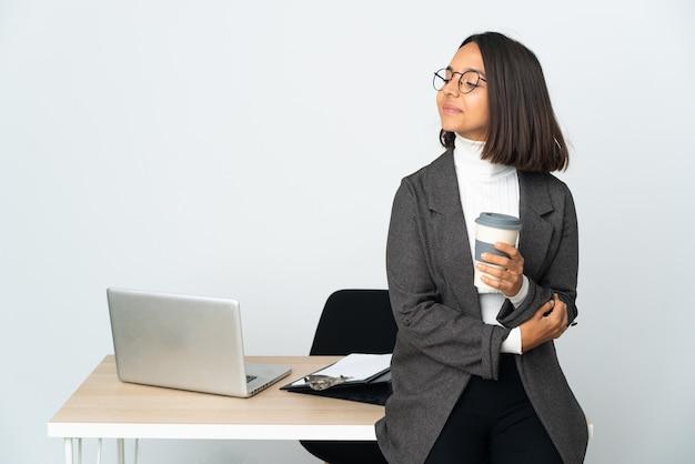 Молодая латинская деловая женщина, работающая в офисе, изолированном на белой стене, глядя в сторону