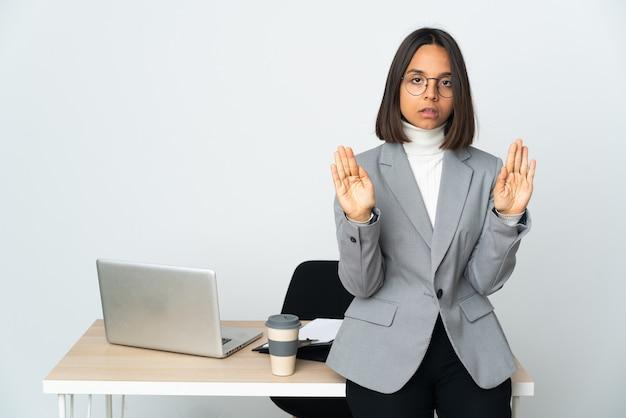 중지 제스처를 만드는 흰 벽에 고립 된 사무실에서 일하고 실망 젊은 라틴 비즈니스 여자