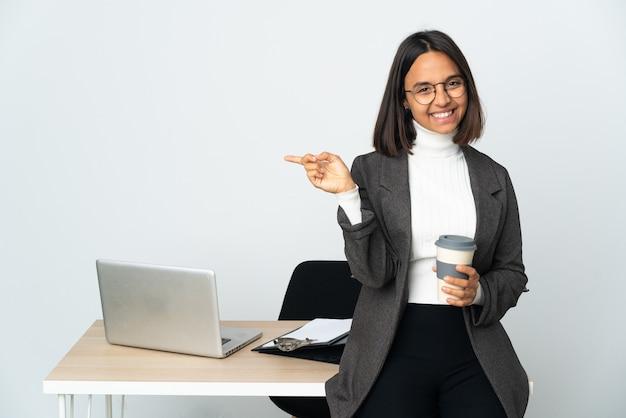 측면에 손가락을 가리키는 흰 벽에 고립 된 사무실에서 일하는 젊은 라틴 비즈니스 여자와 행복