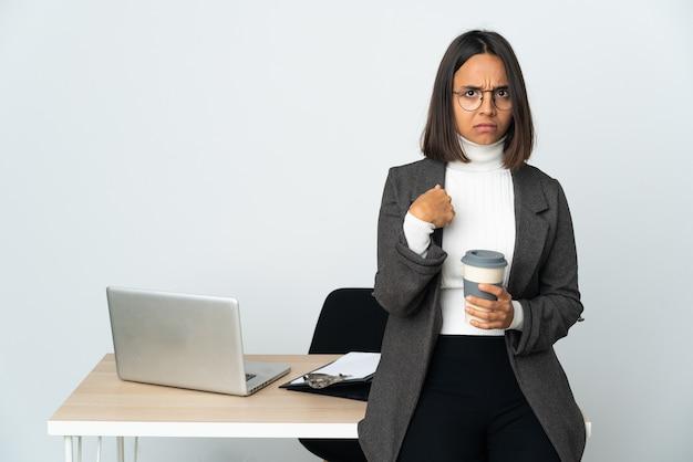자신을 가리키는 흰 벽에 고립 된 사무실에서 일하는 젊은 라틴 비즈니스 우먼