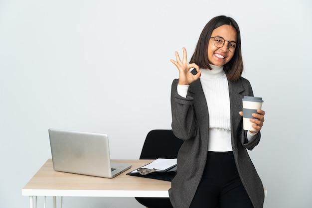 손가락으로 확인 표시를 보여주는 흰 벽에 고립 된 사무실에서 일하는 젊은 라틴 비즈니스 여자