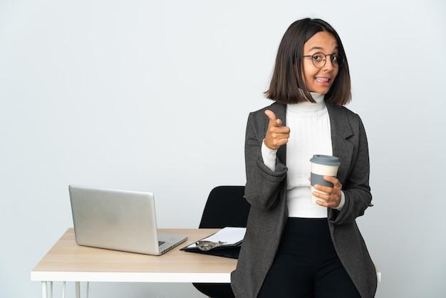 흰 벽에 고립 된 사무실에서 일하고 젊은 라틴 비즈니스 여자는 놀라게하고 앞을 가리키는